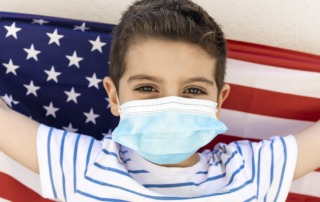 Child wearing face mask while holding American Flag
