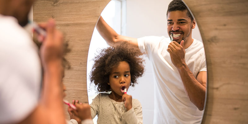 Child and father brushing teeth