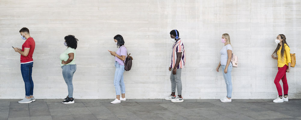 People in line standing 6 feet apart, each wearing a cloth face covering.