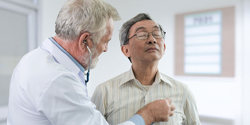 Doctor taking blood pressure of elderly patient