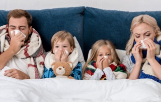 A family in bed together, sick with flu