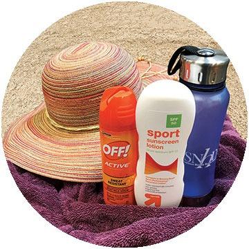 Hat, sunscreen, bug spray, and towel on a sandy beach