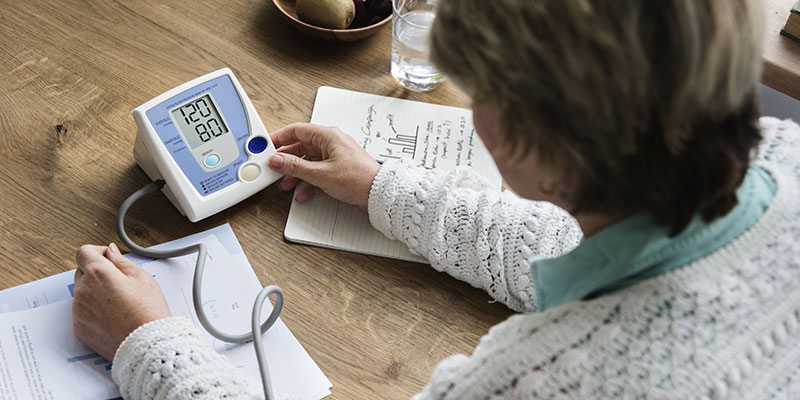 Woman checking her own blood pressure