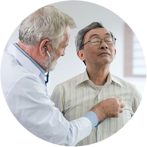 Doctor listens to heart of older male patient