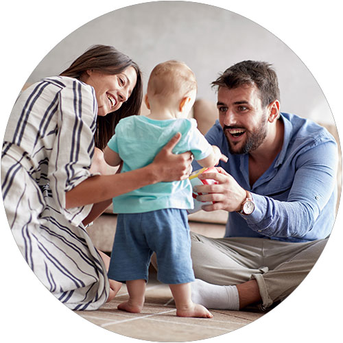 Young mother and father play with their infant
